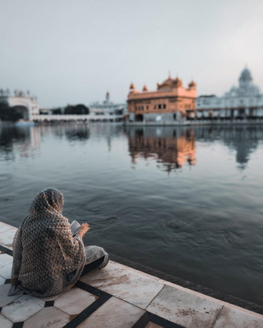 unrecognizable woman sitting near pond